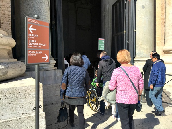 Signs pointing toward different entrances on St. Peter's Basilica || photo by Jessica Spiegel : all rights reserved : may not be used without permission